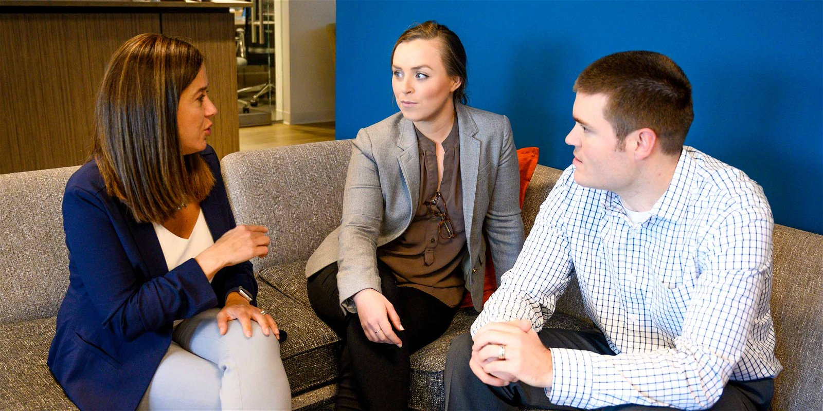 Linkage employees sit on office couch to chat