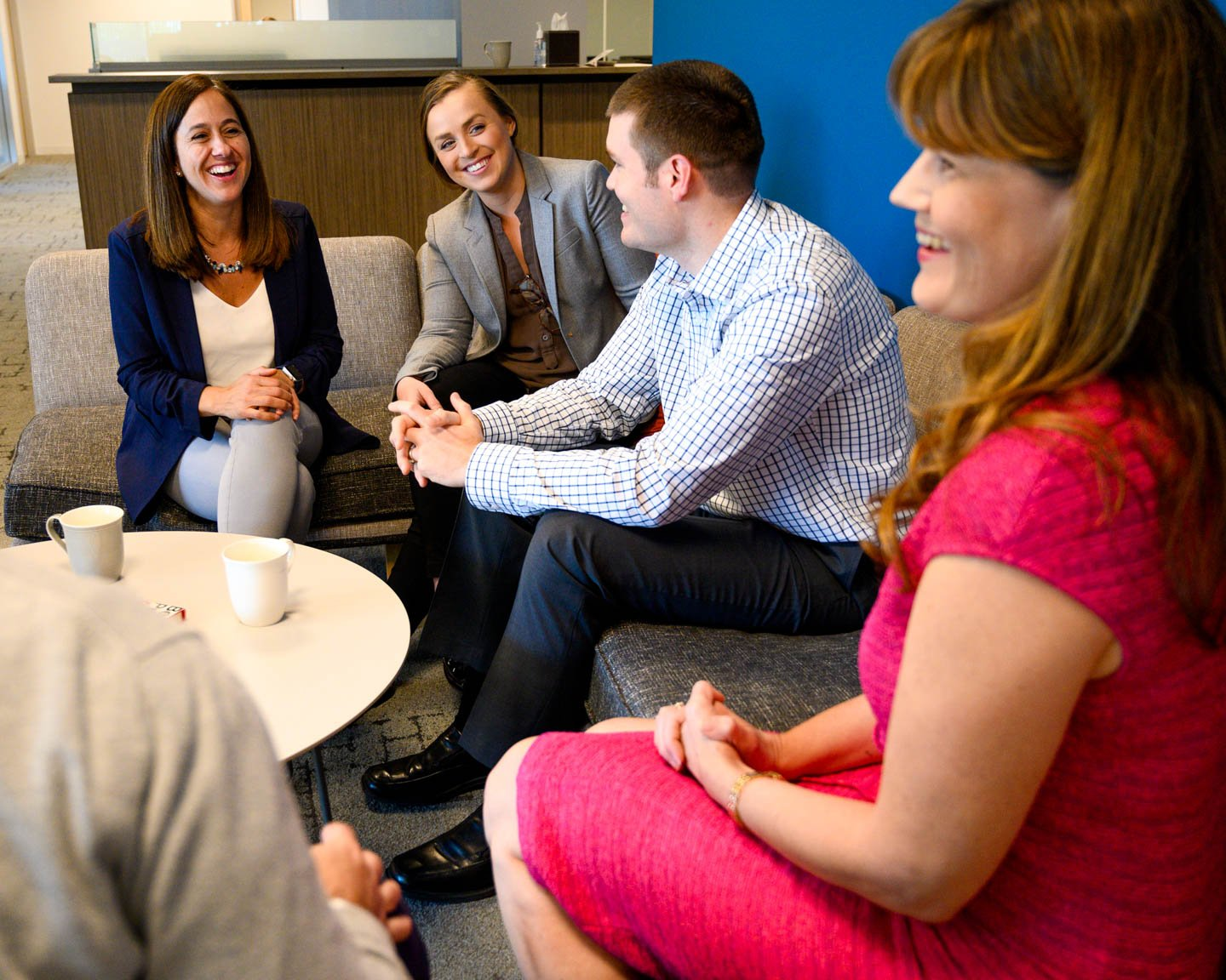Group of employees converse on office couches