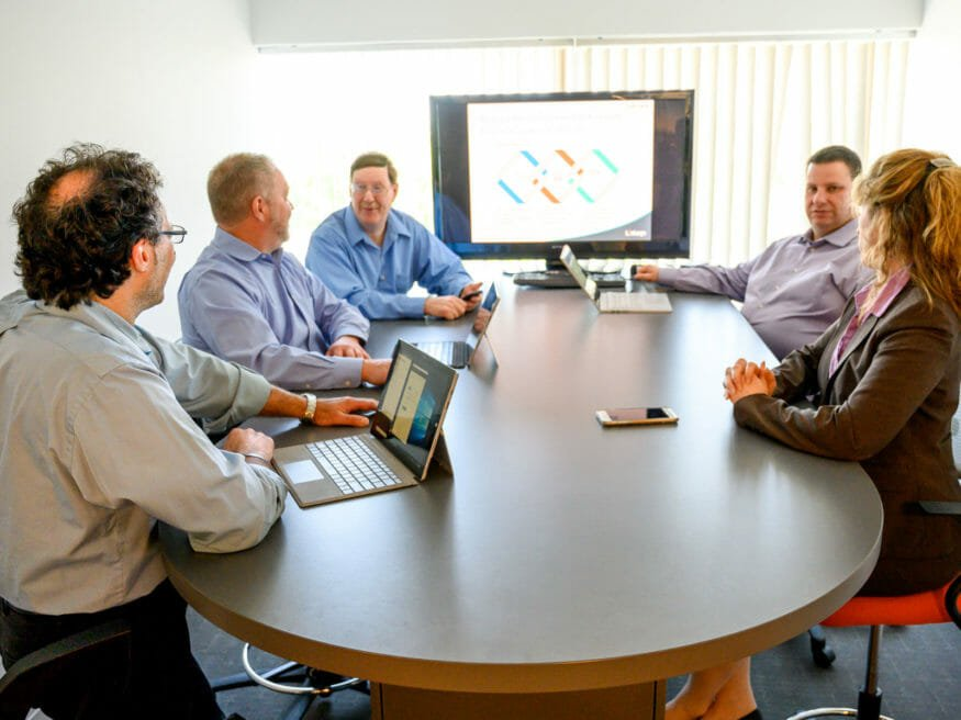 Group sits around table with tablets for meeting