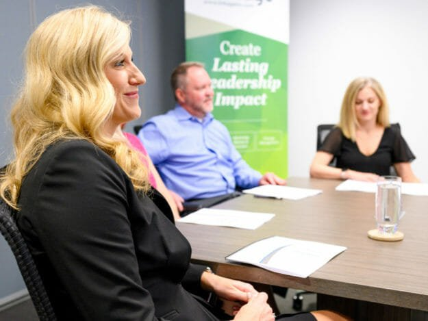Smiling woman sits at table in conference room