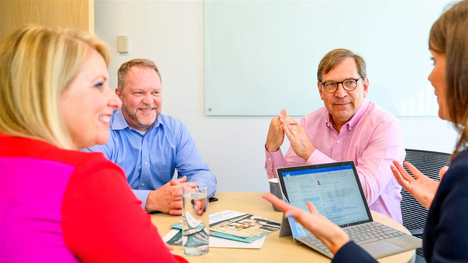 Business leaders sit around table in bright room