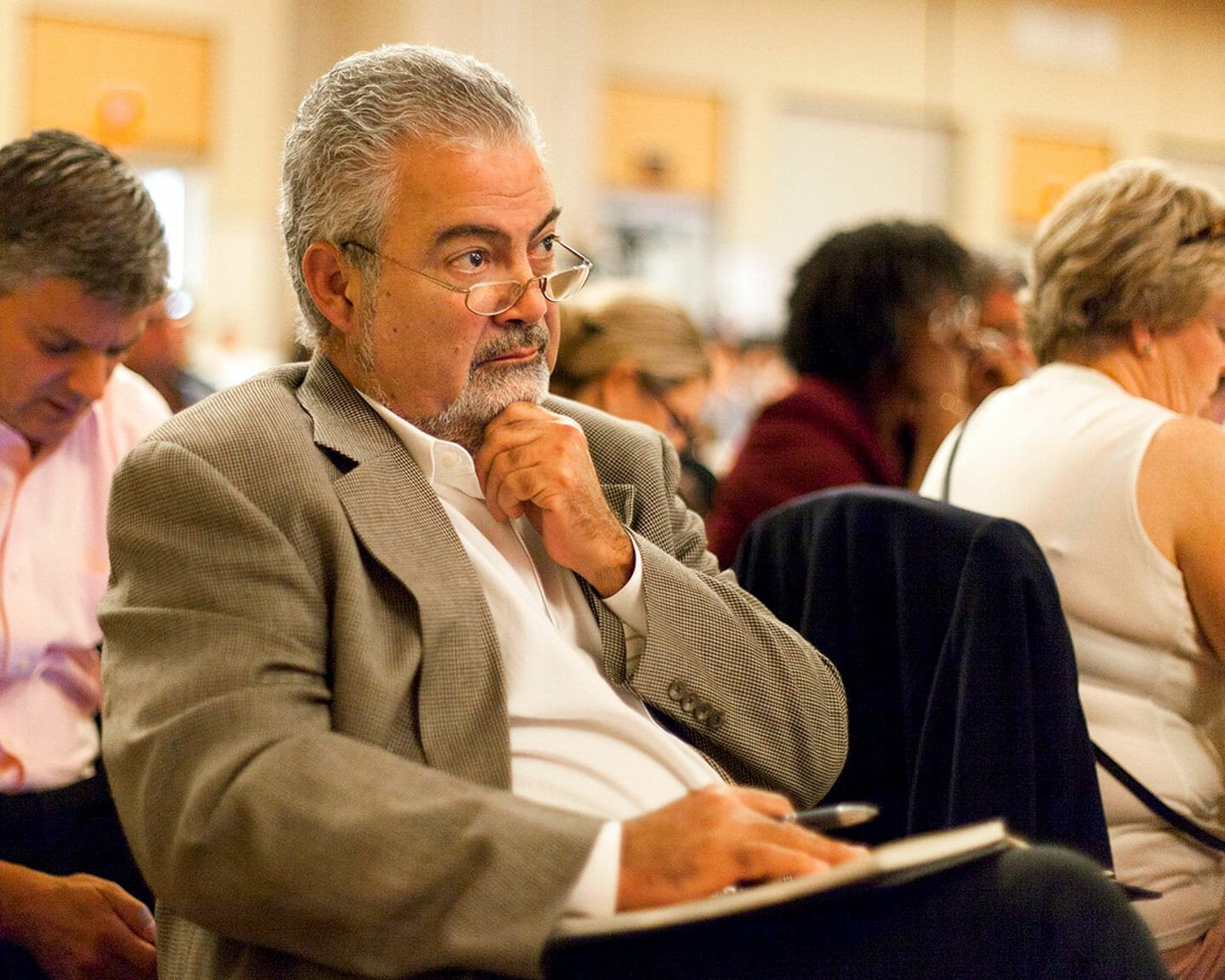 Man at conference watches thoughtfully