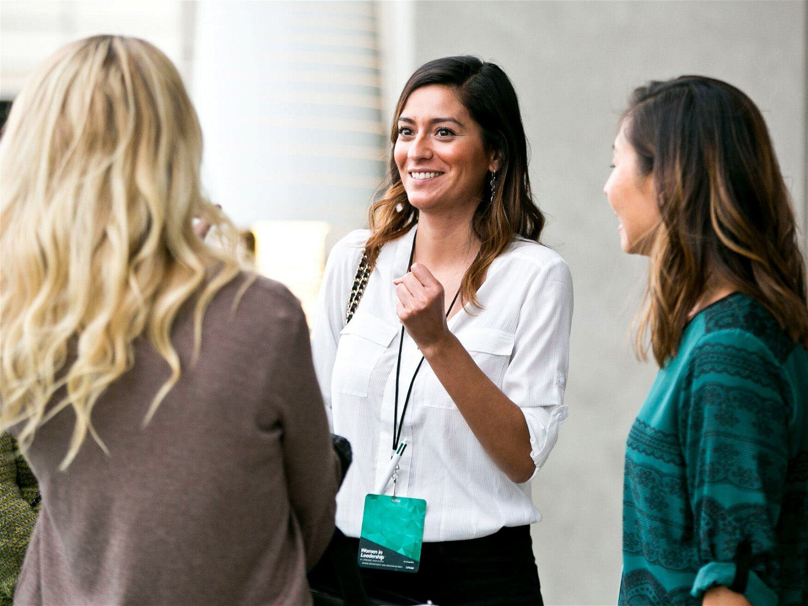 Three female professionals talk outside