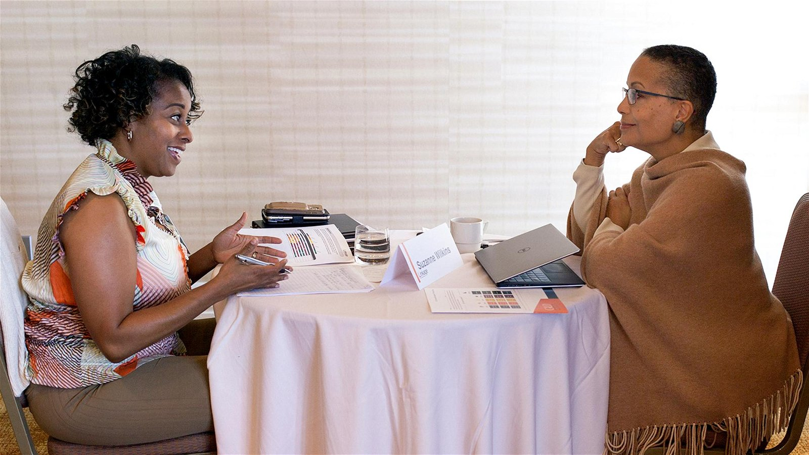 Two women have discussion over small table