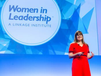 Woman in red dress speaks in front of WIL logo