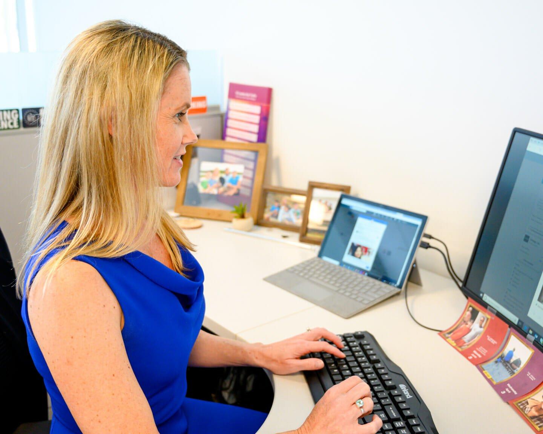 Smiling woman sits at computer desk