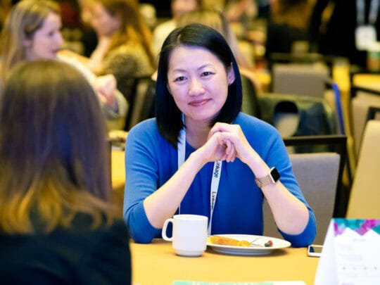 Woman in blue shirt holds hands together at conference table