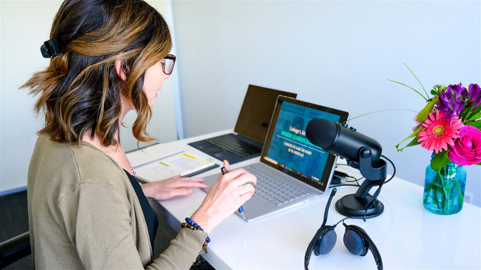 Woman sits at laptop with microphone