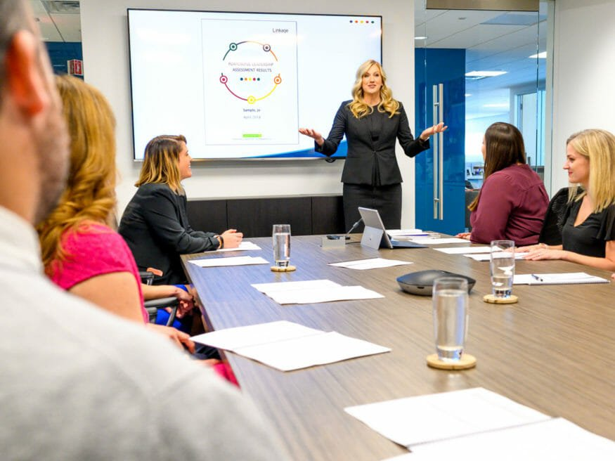 Woman stands in front of screen to lead meeting