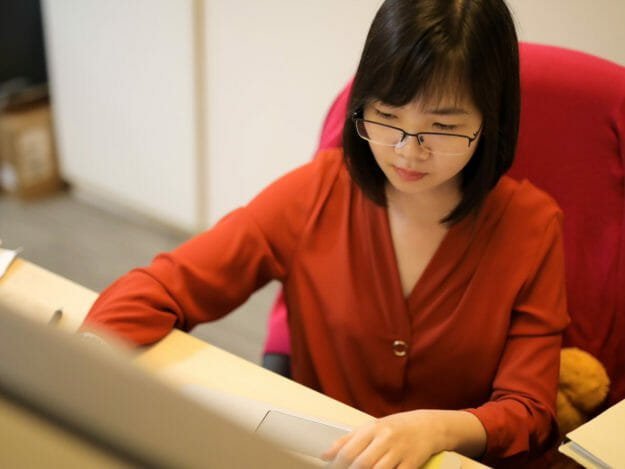 Top-down view of woman in red shirt sitting at desk