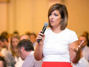 Woman speaks into microphone at Linkage conference