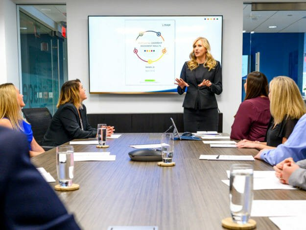 Woman speaks to group seated at conference room table
