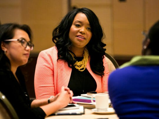 Woman smiles while listening at table during conference