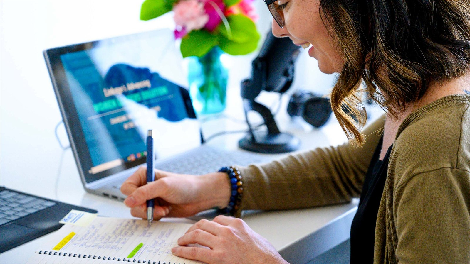 Woman writes in notebook at desk