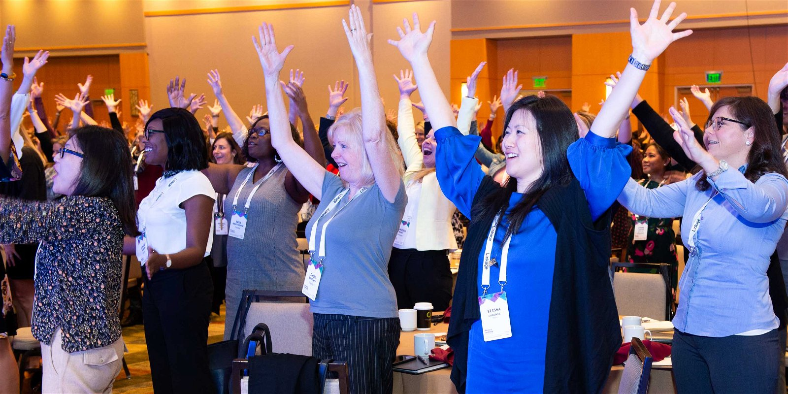 Group of women at conference stand with hands up