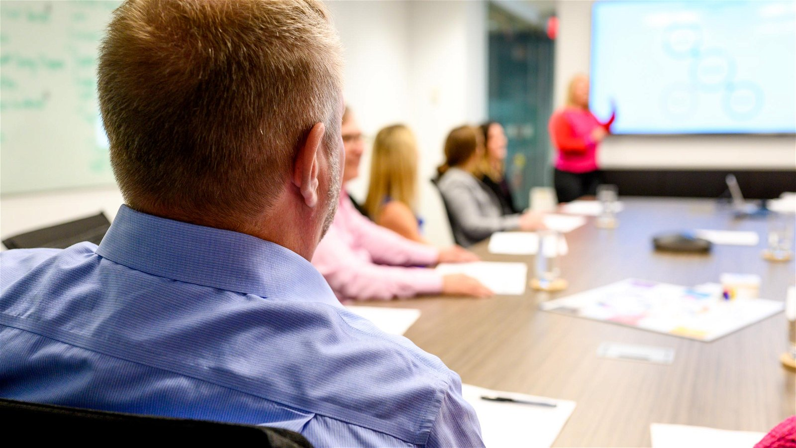 Man's back in forefront at meeting table presentation
