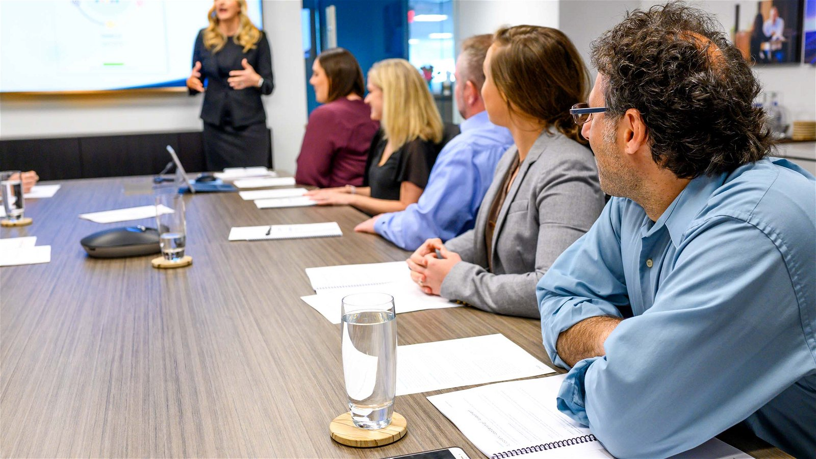 People sit around meeting table while woman presents