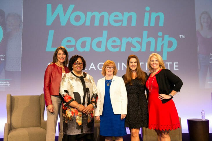 Group stands on stage of Women in Leadership conference