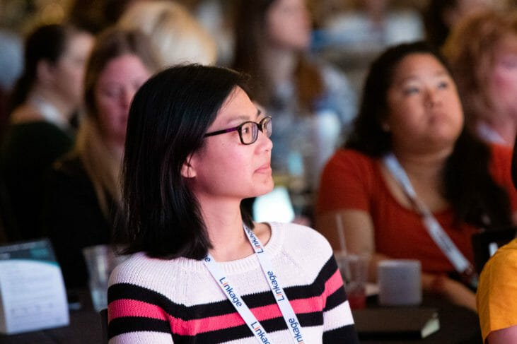 Dark haired woman watches from audience of conference event