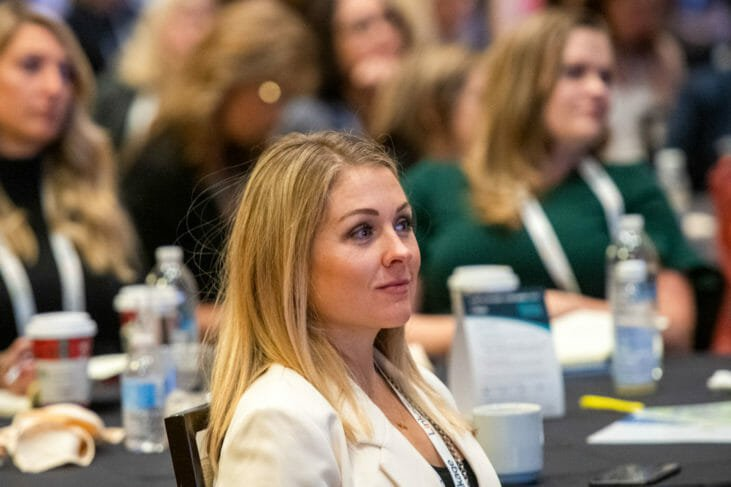 Blonde woman watches conference event