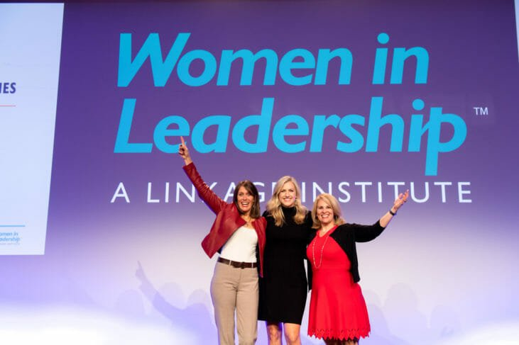 Three women raise arms on stage at conference