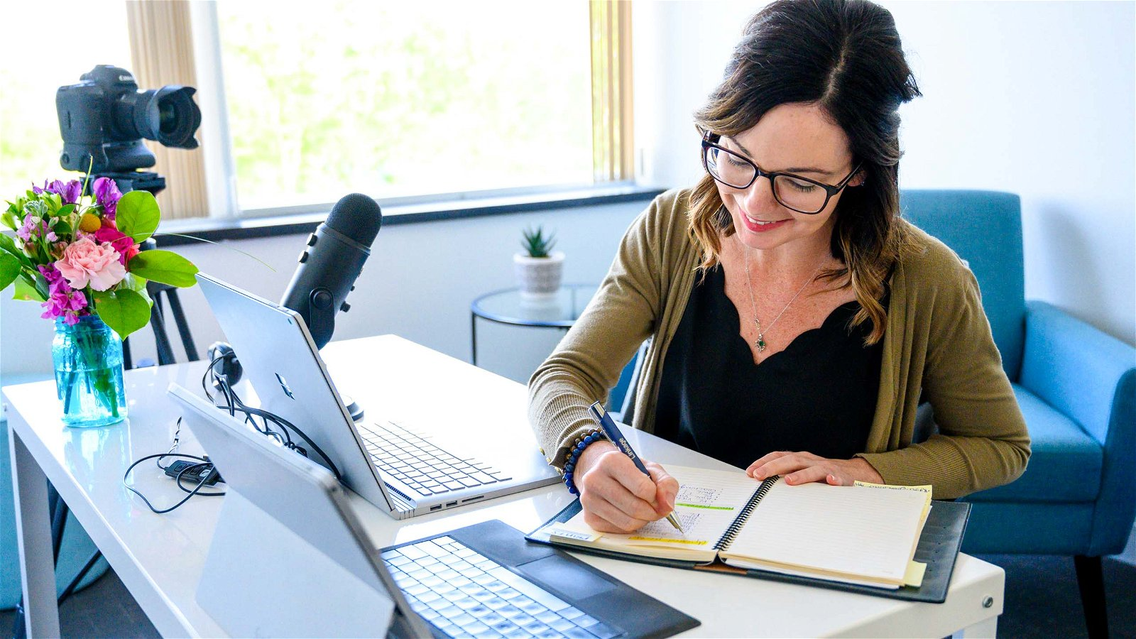 Smiling woman writes in notebook near computer
