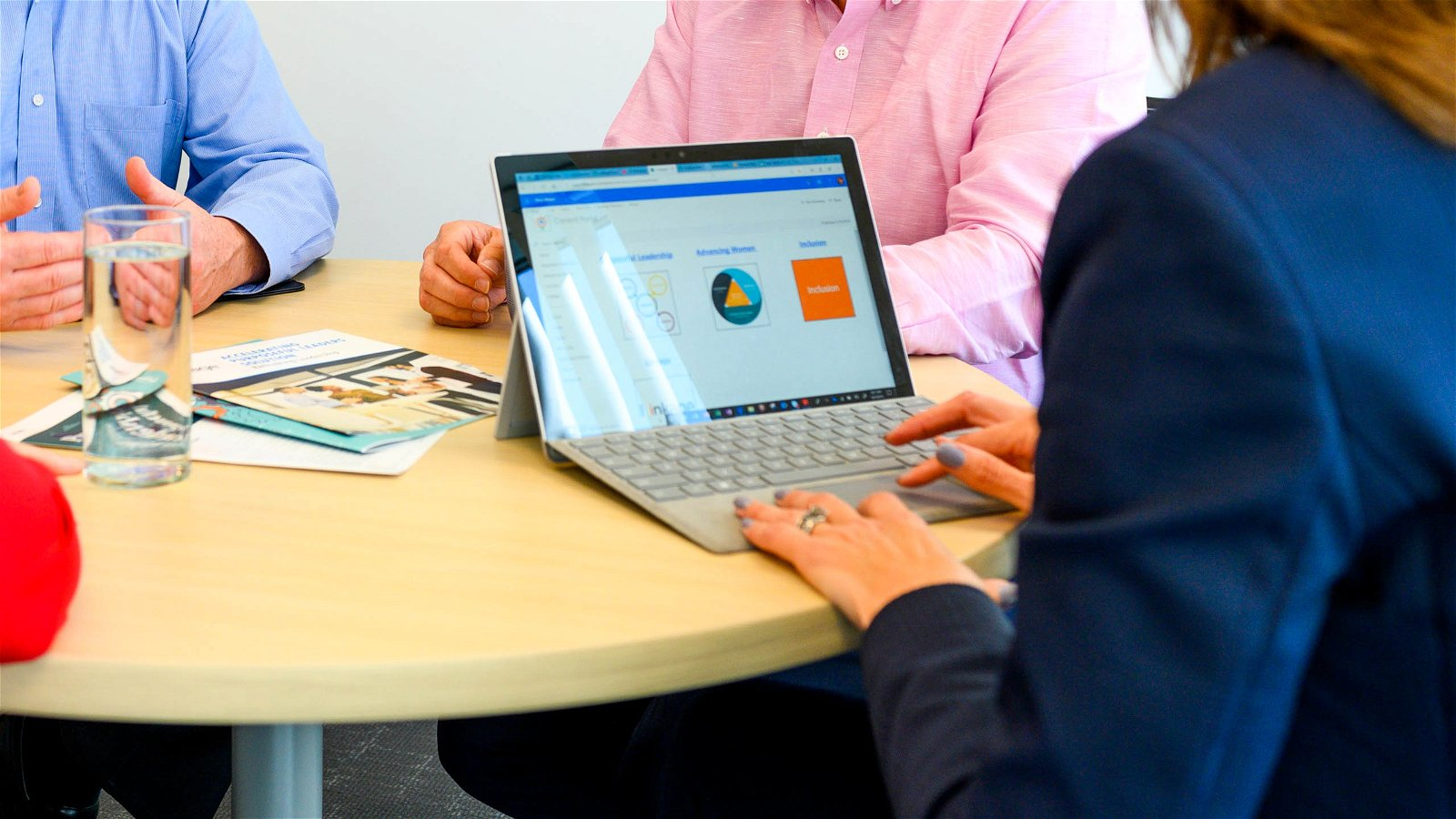 Woman types on Surface during meeting