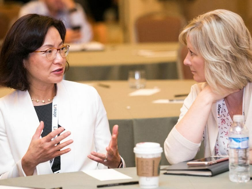 Two women talk at table during Linkage conference